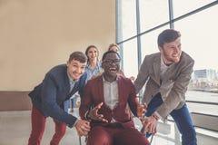 Gens d'affaires enthousiastes réussis de groupe d'équipe de collègue de poussée s'asseyant dans la chaise Images stock