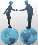 Gens d'affaires est-ouest sur des globes du monde Photos stock
