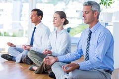 Gens d'affaires faisant le yoga sur le plancher Photographie stock