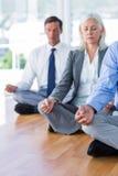 Gens d'affaires faisant le yoga sur le plancher Photo stock