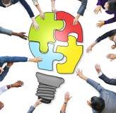 Gens d'affaires formant un puzzle d'ampoule Photographie stock