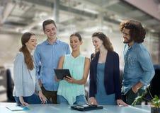 Gens d'affaires heureux à un bureau regardant un comprimé Photos libres de droits