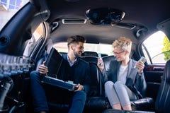 Gens d'affaires heureux dans la limousine complètement de l'argent liquide Photo libre de droits