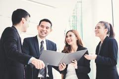Gens d'affaires heureux discutant le travail dans le couloir de bâtiment Photos stock