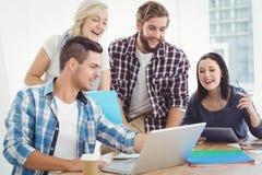 Gens d'affaires heureux travaillant sur l'ordinateur portable Photographie stock
