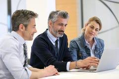 Gens d'affaires lors d'une réunion de travail avec l'ordinateur portable photos libres de droits