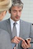Gens d'affaires mûrs échangeant des numéros de téléphone Image libre de droits