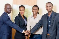 Gens d'affaires mettant leurs mains au-dessus de l'un l'autre dans l'offi photographie stock