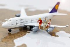Gens d'affaires miniatures avec se reposer sur l'avion Déplacement ou image stock