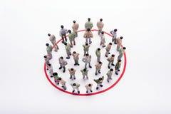 Gens d'affaires miniatures se tenant en cercle au-dessus de contexte Images stock