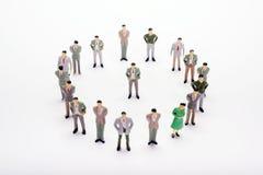 Gens d'affaires miniatures se tenant en cercle au-dessus de contexte ou de Ba Photo libre de droits