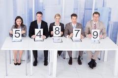 Gens d'affaires montrant des cartes de score Photographie stock libre de droits