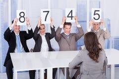 Gens d'affaires montrant des cartes de score devant le candidat féminin Images stock