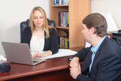 Gens d'affaires parlant au-dessus de l'ordinateur portable à la table image stock