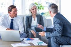 Gens d'affaires parlant ensemble du divan Photo stock