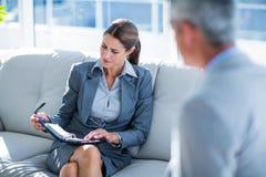 Gens d'affaires parlant ensemble du divan Image stock