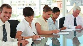 Gens d'affaires prenant des notes tout en se reposant à une table de réunion banque de vidéos
