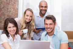 Gens d'affaires regardant l'appareil-photo derrière un ordinateur portable Photographie stock libre de droits