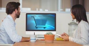 Gens d'affaires regardant l'icône de chariot sur l'écran de moniteur Photographie stock