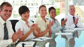 Gens d'affaires s'asseyant à des applaudissements de table de réunion banque de vidéos