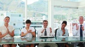 Gens d'affaires s'asseyant dans la ligne à des applaudissements de table banque de vidéos