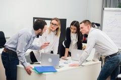 Gens d'affaires s'asseyant dans le bureau au cours de la réunion et discutant avec des écritures utilisant des ordinateurs portab photos stock