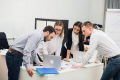 Gens d'affaires s'asseyant dans le bureau au cours de la réunion et discutant avec des écritures utilisant des ordinateurs portab photo libre de droits