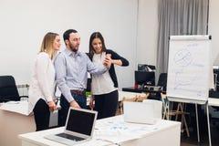 Gens d'affaires s'asseyant dans le bureau au cours de la réunion et discutant avec des écritures utilisant des ordinateurs portab photo stock