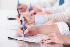 Gens d'affaires s'asseyant dans une ligne et écrivant des notes Photo stock