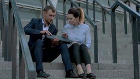 Gens d'affaires s'asseyant sur des escaliers banque de vidéos