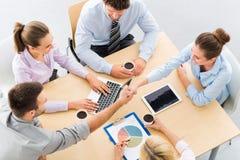 Gens d'affaires se serrant la main à travers la table photos libres de droits