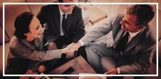 Gens d'affaires se serrant la main tout en travaillant image stock