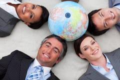Gens d'affaires se trouvant sur l'étage autour d'un globe photographie stock