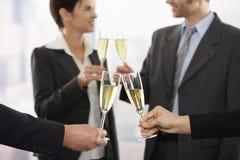 Gens d'affaires soulevant le pain grillé avec le champagne Photo stock