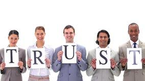 Gens d'affaires tenant des conseils avec le mot CONFIANCE Image libre de droits