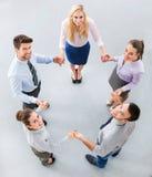 Gens d'affaires tenant des mains pour former un cercle Photographie stock libre de droits