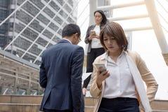 Gens d'affaires tenant le téléphone portable et marchant sur un passage couvert moderne photographie stock