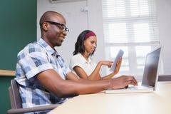 Gens d'affaires travaillant à un ordinateur portable et à un comprimé Images stock