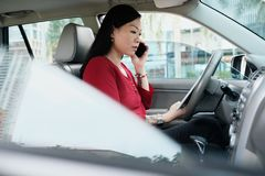 Gens d'affaires travaillant dans la voiture et parlant au téléphone portable Image stock