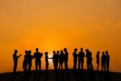 Gens d'affaires travaillant dehors avec vue sur le coucher du soleil Photos stock