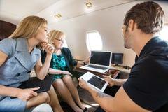 Gens d'affaires travaillant ensemble dans le jet privé photographie stock libre de droits