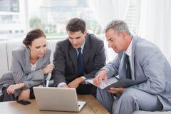 Gens d'affaires travaillant ensemble sur leur ordinateur portable Photographie stock libre de droits