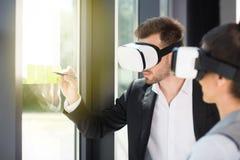 Gens d'affaires utilisant des casques de réalité virtuelle tout en travaillant dans le bureau Images stock