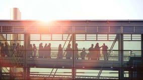 Gens d'affaires waling à l'intérieur de du bâtiment en verre de couloir Ciel de coucher du soleil clips vidéos
