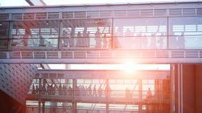 Gens d'affaires waling le bâtiment en verre moderne de couloir de cuvette Ciel de coucher du soleil banque de vidéos