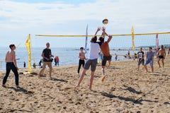 Gens du commun jouant le volleyball de plage sur le bord de la mer Images stock