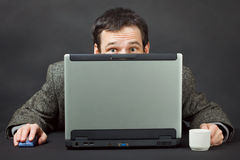 Gens effrayés se cachant derrière l'écran d'ordinateur Photo libre de droits