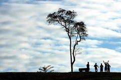 Gens et arbre de silhouette Image libre de droits