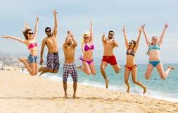 Gens heureux branchant sur une plage Image stock