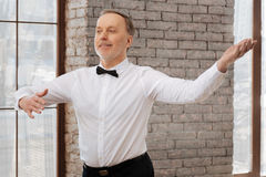 Gent bearded aging man rehearsing classical dance at the ballroom. Looking for a perfect dance partner. Handsome delighted skilled aging man performing in the stock photo